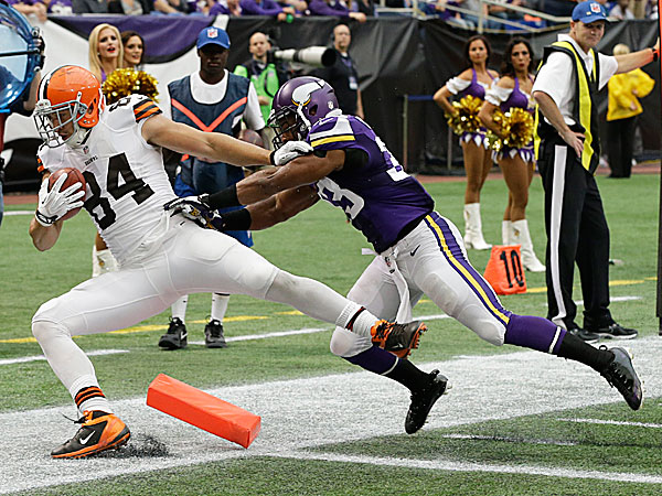 Browns tight end Jordan Cameron is pushed out of the end zone by Vikings strong safety Jamarca Sanford after catching on an 11-yard touchdown pass. (Jim Mone/AP)
