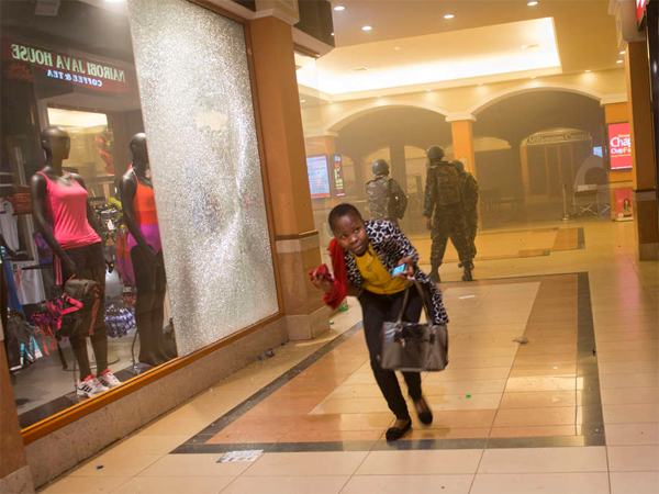 A woman who had been hiding during the gun battle runs for cover after armed police, seen behind, enter the Westgate Mall in Nairobi. Attackers targeted non-Muslims at the upscale mall.