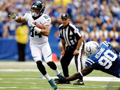 Jacksonville Jaguars wide receiver Cecil Shorts (84) attempts to avoid the tackle of Indianapolis Colts defensive end Cory Redding. (AP Photo/Michael Conroy)
