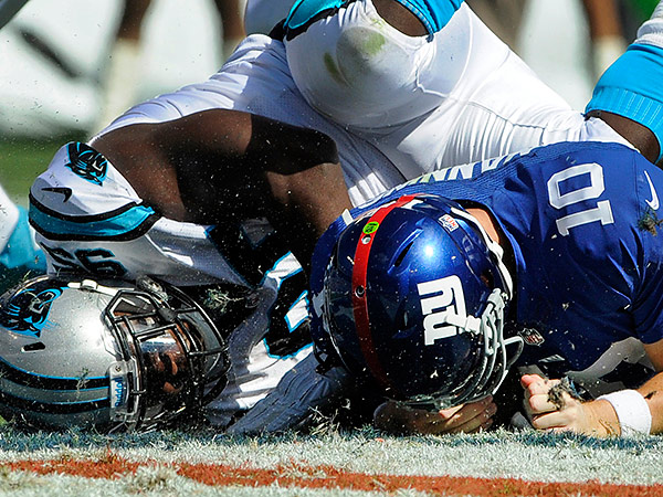 New York Giants quarterback Eli Manning takes a faceplant courtesy of Carolina´s Charles Johnson. (Mike McCarn/AP)