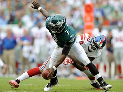 Michael Vick scrambles away from Giants´ defensive end Jason Pierre-Paul in the first half. (Michael Perez/AP)