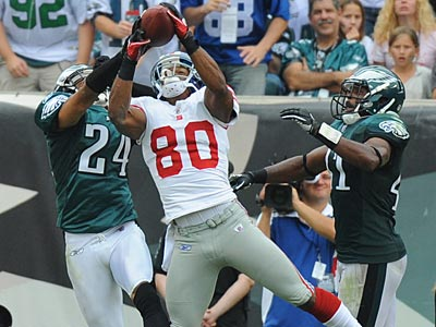 Victor Cruz catches a touchdown pass in between Nnamdi Asomugha and Jarrad Page. (Clem Murray/Staff Photographer)