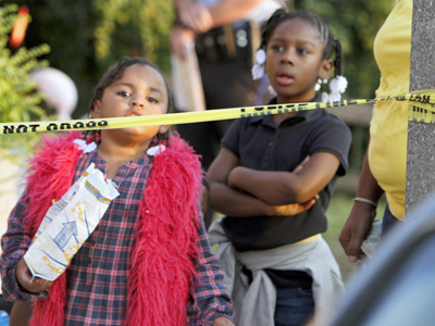 Children watch investigators on the 7300 block of Theodore Street, in the Eastwick section of Southwest Philadelphia on Tuesday, Sept. 25, after a woman was shot to death and her 5-year-old daughter received a graze wound to the head. (For the Daily News/ Joseph Kaczmarek)