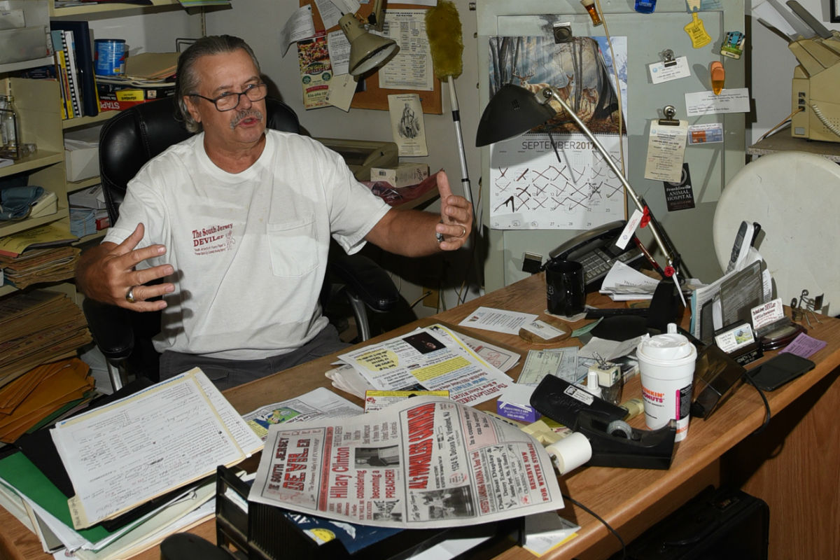 """Ken Camp, a retired helicopter pilot, is a comedian and newspaper publisher in rural South Jersey. He talks in his home-office, surrounded by memorabilia and mounted hunting trophies. Every month, he sends out 20,000 copies of his South Jersey Devil-er, the self-proclaimed best newspaper in the world. It´s full of jokes, many off color, and lots of motivational quotes and lots of ads for taxidermists and fishing stores. Camp says no one ever complains, but if they do, he publishes the complaints too. He said he´s one of only about 12 """"funny papers"""" that publish in the country including The Onion. His recent headlines included: Hillary Clinton considering becoming a preachers and tons of corny jokes. He´s been publishing for 16 years."""