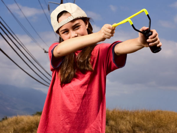 A young tomboy plays with a slingshot. (iStock photo)