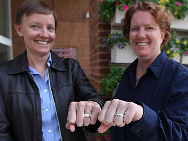 Isabelle Barker, left, and Cara Palladino, right, show off their wedding rings they exchanged when they were legally married in the State of Massachusetts.  Two Pennsylvania women have filed a federal lawsuit seeking national recognition of same-sex marriage. Though married in Massachusetts, Cara Palladino and Isabelle Barker say their status is not recognized in Pennsylvania, where they now live with a four-year-old son. Marriages of same-sex couples in 13 states and the District of Columbia are not recognized in the other 37 states. The suit seeks to change this.	 09/26/ 2013 ( MICHAEL BRYANT / Staff Photographer  )