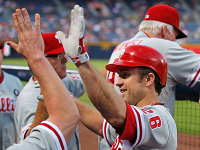 Chase Utley celebrates in the dugout after hitting a home run in the first inning. (John Bazemore/AP)