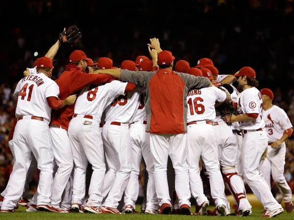 Members of the St. Louis Cardinals celebrate after the Cardinals´ 7-0 win over the Chicago Cubs in a baseball game to clinch the NL Central title Friday, Sept. 27, 2013, in St. Louis. (Jeff Roberson/AP)