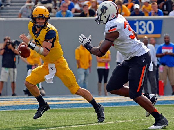 West Virginia quarterback Clint Trickett (9) avoids the pass rush in the third quarter of an NCAA college football game against Oklahoma State in Morgantown, W.Va., on Saturday, Sept. 28, 2013. (Tyler Evert/AP)