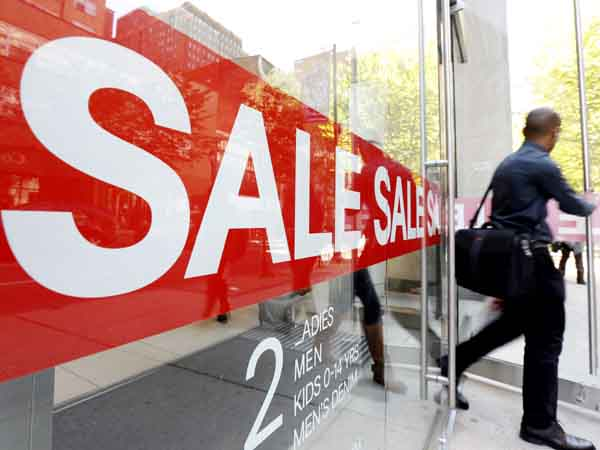 In this Wednesday, Sept. 18, 2013 photo, a consumer exits a store with a sale sign posted in the windows in Philadelphia. The government reports how much consumers spent and earned in August on Friday, Sept. 27, 2013. (AP Photo/Matt Rourke)