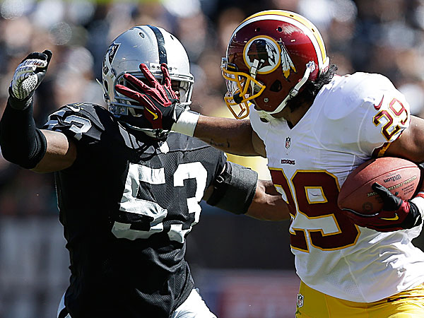 Redskins running back Roy Helu stiff-arms Raiders linebacker Nick Roach during the second quarter. (Marcio Jose Sanchez/AP)