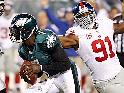Eagles quarterback Michael Vick attempts to elude Giants defensive end Justin Tuck. (Yong Kim/Staff Photographer)