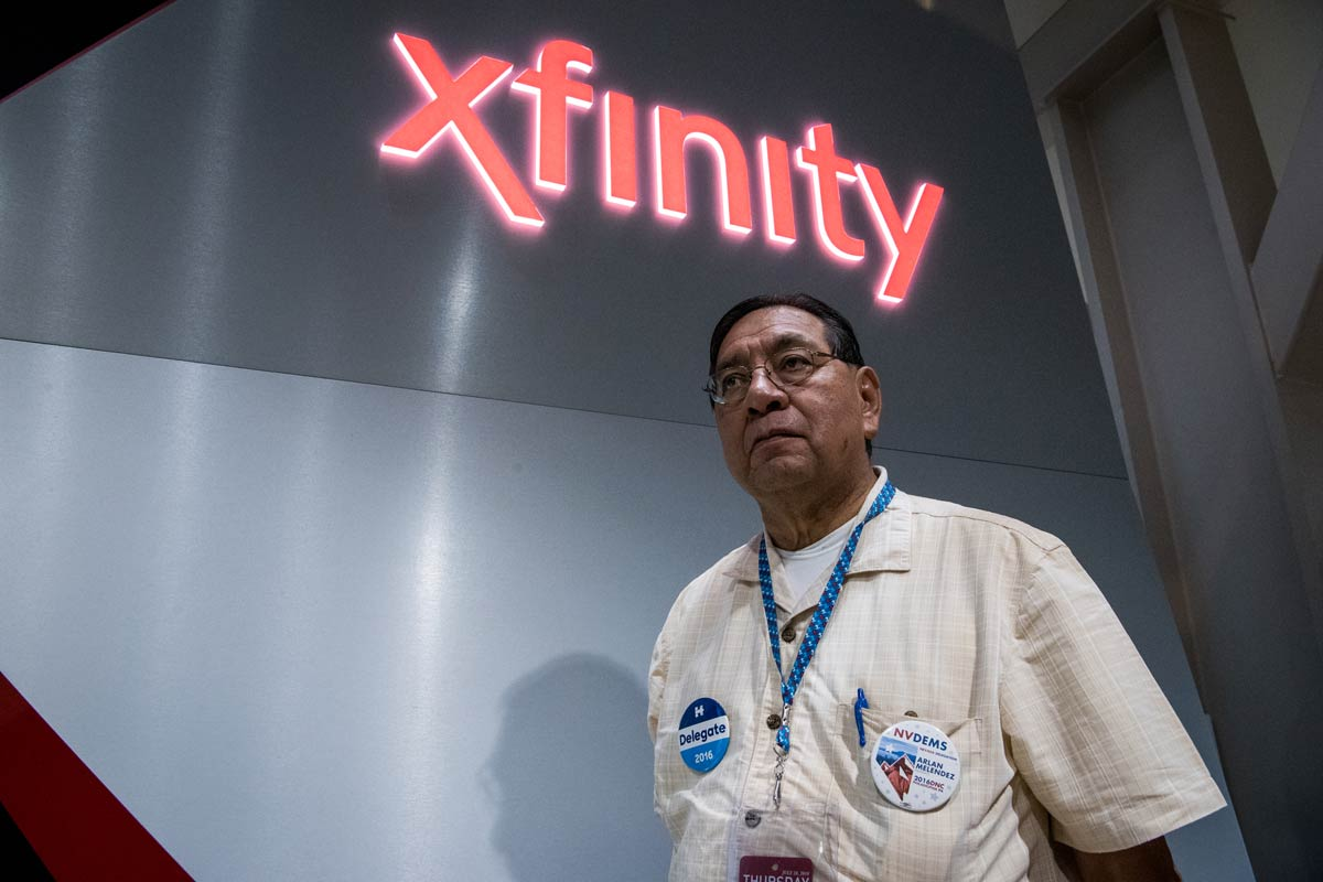 Arlan Melendez, 68, a delegate from Nevada, stands underneath an Xfinity sign inside the Wells Fargo Center on Thursday, July 28, 2016.