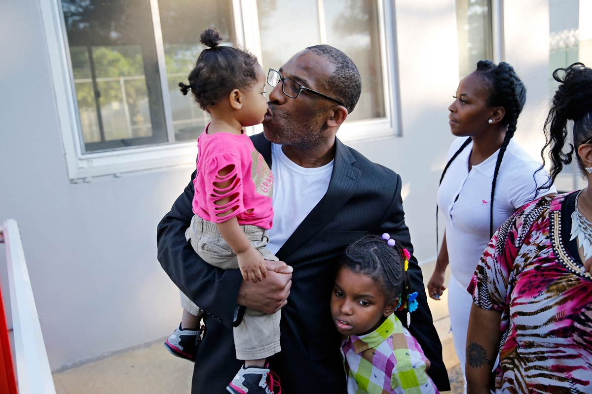 Anthony Wright steals a kiss from his granddaughter Romera Wright, 1, and holds on tight to his other granddaughter, Daria Wright, 8, as he spends time with his family after walking out of Curran-Fromhold Correctional Facility on Tuesday, Aug. 23, 2016.