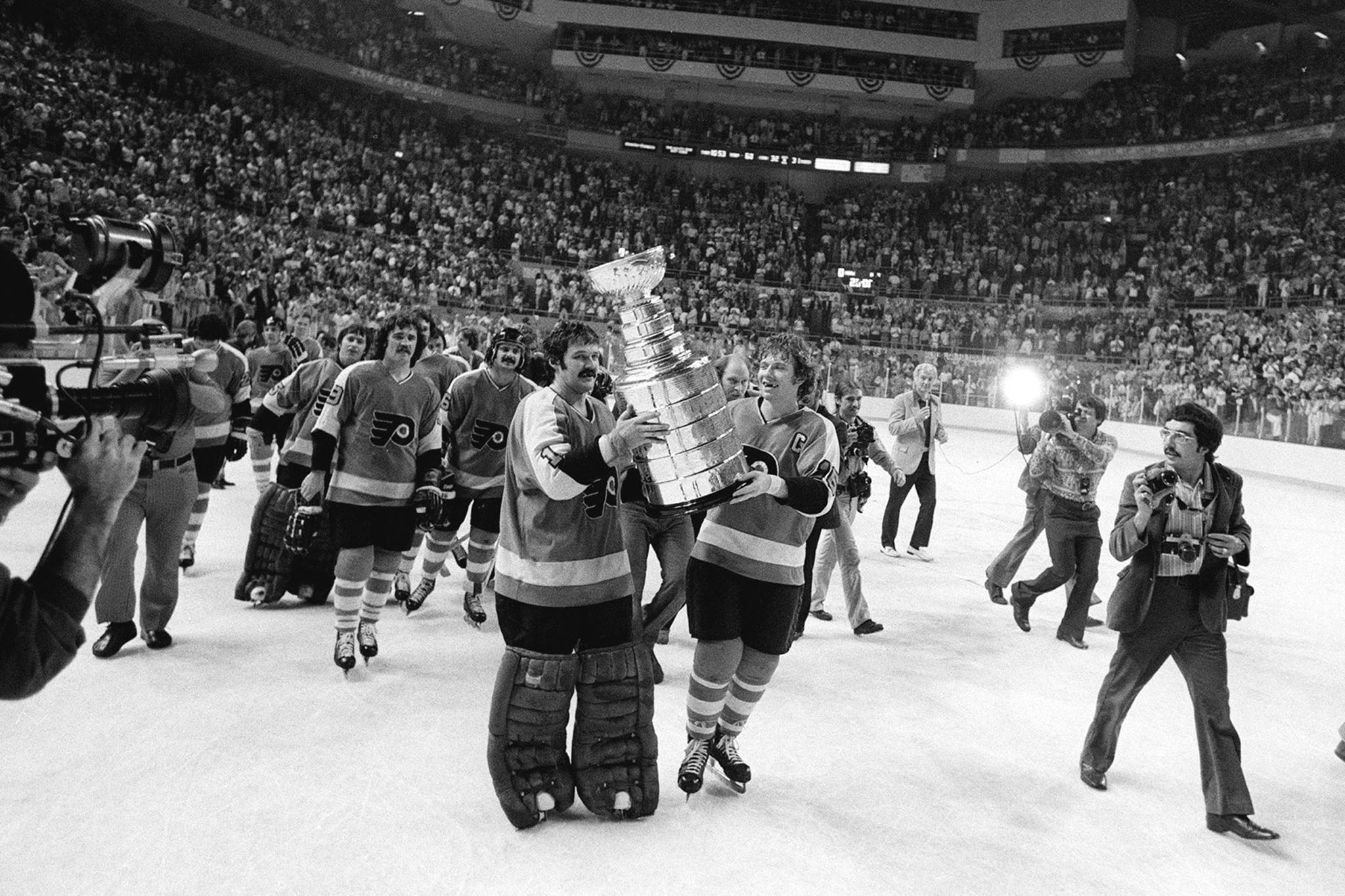 Flyers goalie Bernie Parent and captain Bob Clarke carry the Stanley Cup triumphantly around the Memorial Auditorium in Buffalo, after winning the 1975 finals against the Sabres in Game 6.