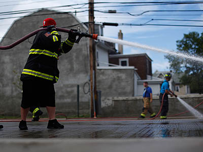 Firefighters spray away the mud in the aftermath of a flood  in Darby on Friday. (AP Photo / Matt Rourke)
