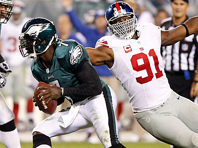 Michael Vick avoids Giants defensive lineman Justin Tuck during the<br />fourth quarter. (Yong Kim/Staff Photographer)