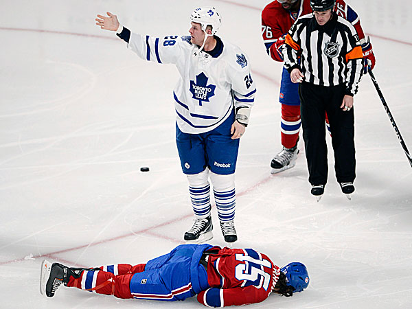 Maple Leafs right wing Colton Orr calls for help for Canadiens right wing George Parros after Parros hit his head on the ice during their fight in the third period. (Ryan Remiorz/The Canadian Press/AP)