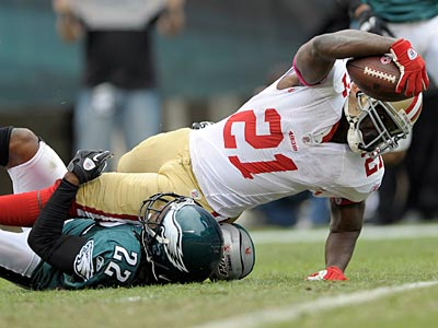 49ers running back Frank Gore scores a touchdown over Eagles cornerback Asante Samuel. (Michael Perez/AP)