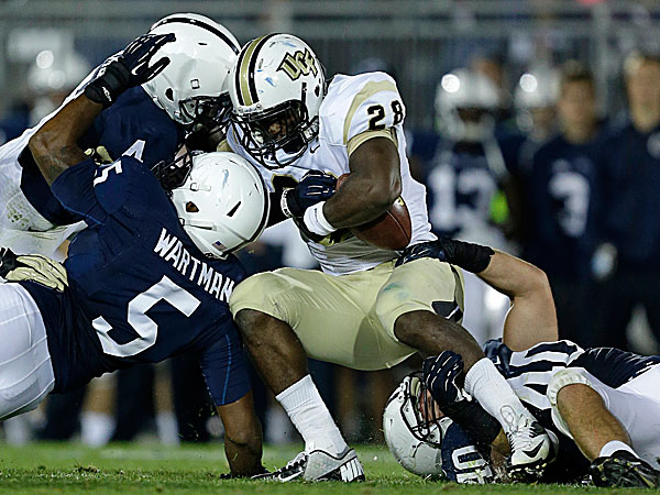 UCF running back William Stanback is brought down by Penn State safety Adrian Amos, linebacker Nyeem Wartman and linebacker Glenn Carson. (Gene J. Puskar/AP)