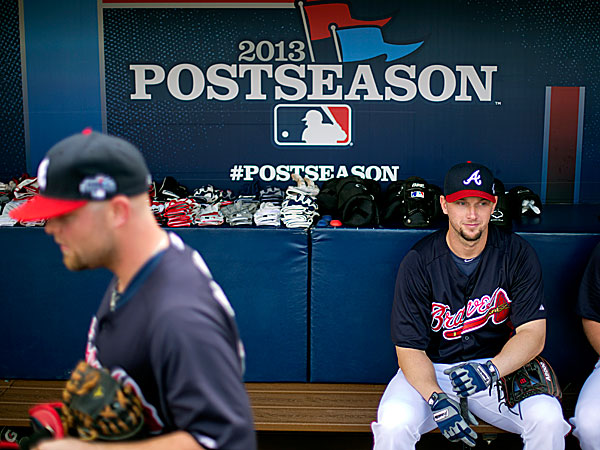 The Braves´ Chris Johnson sits in the dugout as teammate Brian McCann passes by during a baseball workout. (David Goldman/AP)