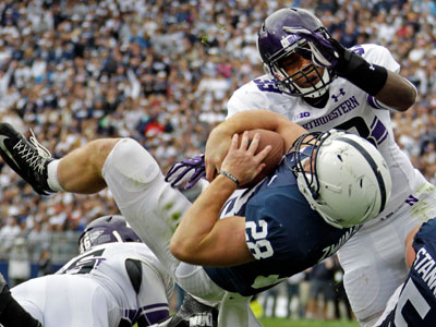 Zach Zwinak dives into the end zone past Northwestern linebacker David Nwabuisi for a touchdown on Saturday. (Gene J. Puskar/AP)