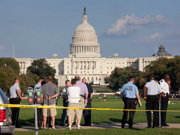 Law enforcement officers are near the scene on the National Mall in Washington, where a man set himself on fire Friday, Oct. 4, 2013. (AP Photo/J. Scott Applewhite)