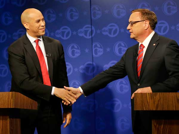 Democrat Cory Booker, left, and Republican Steve Lonegan shake hands before their first debate of the U.S. Senate campaign in Trenton, N.J., Friday, Oct. 4, 2013. (AP photo)