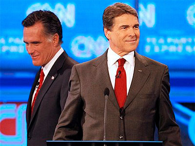 Republican presidential candidate former Massachusetts Gov. Mitt Romney, left, passes behind Texas Gov. Rick Perry during a break in a Republican presidential debate Monday, Sept. 12, 2011, in Tampa, Fla. (AP Photo / Mike Carlson)