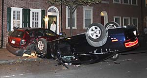 Anne Ewers of Lombard Street looks out her front door at an overturned car that crashed hitting a parked car near 3rd street, Thusday night about 10:30pm, October 11, 2012. The New Jersey driver and two women fled the scene on foot but were apprehended by police a short distance away.    ( STEVEN M. FALK/ Staff Photographer )