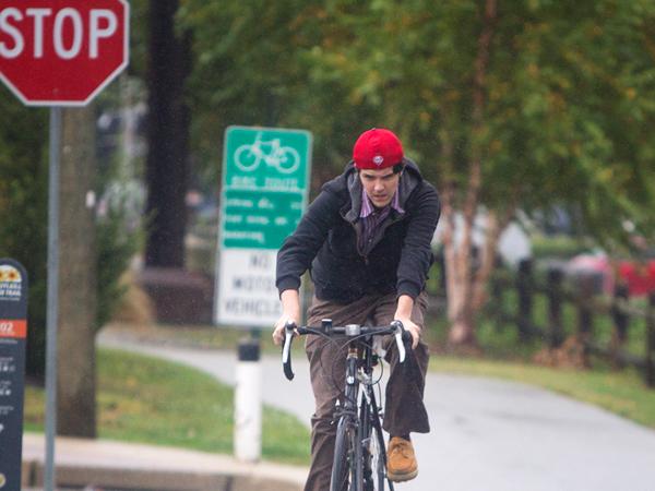 Kevin Readinger, 20 of Conshohocken peddles his bike through the rain on the Schuylkill River trail near its railhead in Conshohocken. (Ed Hille/Staff Photographer)