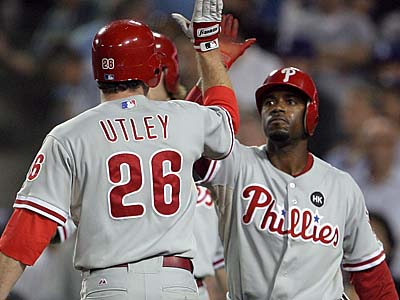 Phillies Chase Utley and Jimmy Rollins celebrate their run score after Ryan Howard hit a fifth inning two run double against the Los Angeles Dodgers in Game 1 of the NLCS at Dodger Stadium.  (Yong Kim / Staff Photographer)