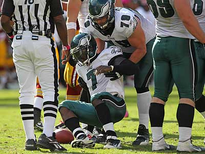 Todd Herremans, seen here helping Michael Vick up, shifted to left tackle with Jason Peters and King Dunlap out. (Michael Bryant/Staff Photographer)