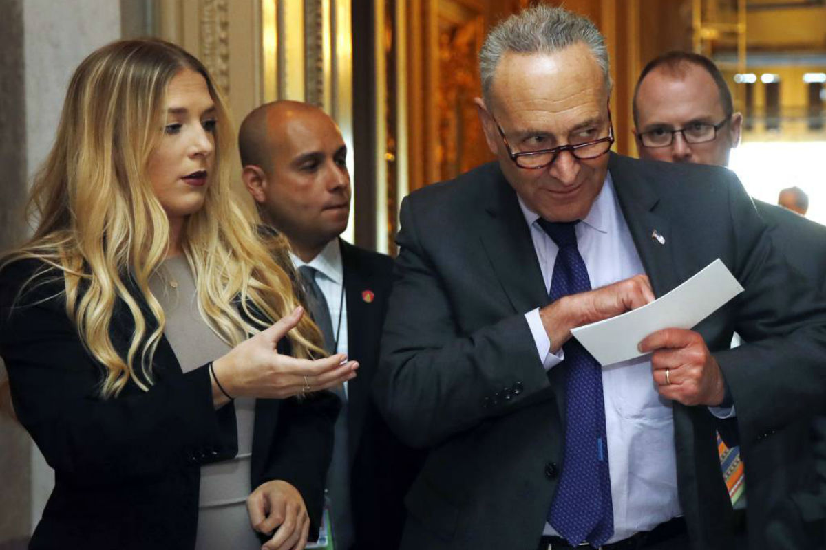 Senate Minority Leader Chuck Schumer of N.Y., right, leaves the Senate floor after a vote, Thursday, Oct. 19, 2017, on Capitol Hill in Washington.