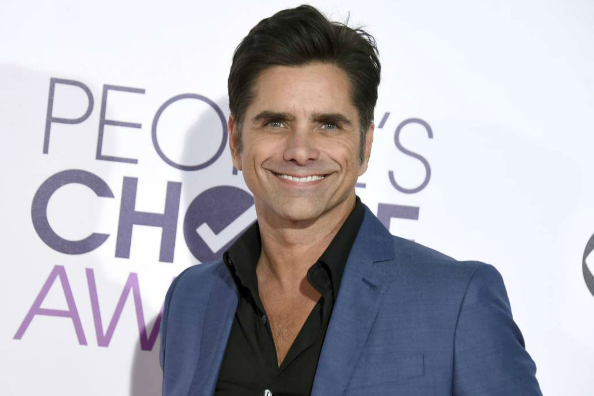 FILE - In this Jan. 18, 2017 file photo, John Stamos arrives at the People´s Choice Awards at the Microsoft Theater in Los Angeles. Stamos announced his engagement to actress Caitlin McHugh on social media Oct. 22, 2017.