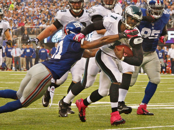 Michael Vick drags a Giants defender. (Ron Cortes/Staff Photographer)