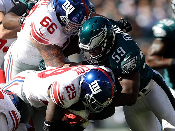 Eagles linebacker DeMeco Ryans tackles Giants running back Michael Cox during the first half. (Matt Rourke/AP)