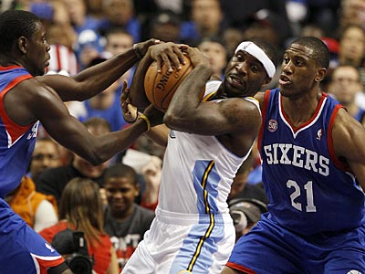 Jrue Holiday and Thaddeus Young double-team the Nuggets´ Ty Lawson during Wednesday´s opener. (Yong Kim/Staff Photographer)