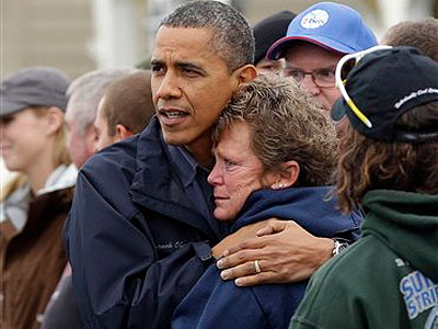 President Barack Obama, left, embraces Donna Vanzant, right, during a tour of a neighborhood effected by superstorm Sandy, Wednesday, Oct. 31, 2012 in Brigantine, N.J.  Vanzant is a owner of North Point Marina, which was damaged by the storm. (AP Photo/P