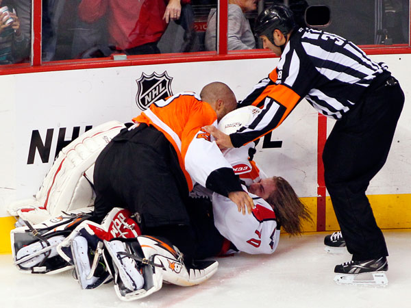 Linesman Francois St. Laurent, right, tries to pull Flyers goalie Ray Emery, top, off of Washington Capitals goalie Braden Holtby during a melee in the third period of an NHL hockey game Friday, Nov. 1, 2013, in Philadelphia. The Capital won 7-0. (Tom Mihalek/AP)