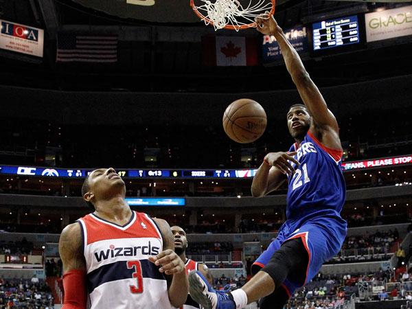 Thaddeus Young (21) dunks over Washington Wizards guard Bradley Beal (3) and forward Trevor Booker (35) in the first half of an NBA basketball game, Friday, Nov. 1, 2013, in Washington. (Alex Brandon/AP)