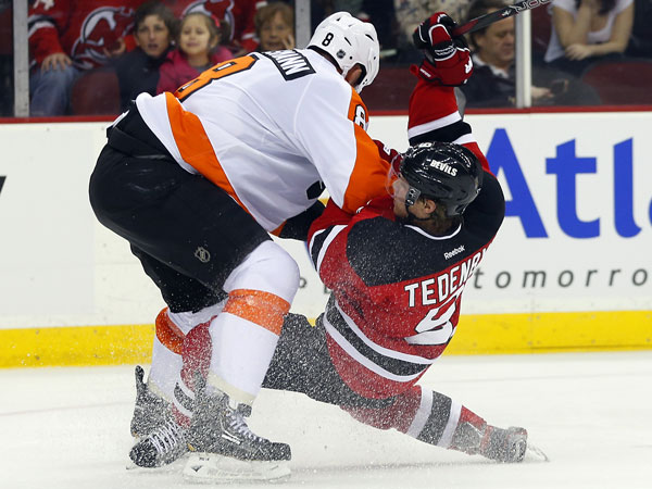 Nicklas Grossmann, left, checks New Jersey Devils´ Mattias Tedenby, of Sweden, to the ice during the second period of an NHL hockey game in Newark, N.J., Saturday, Nov. 2, 2013. (Rich Schultz/AP)