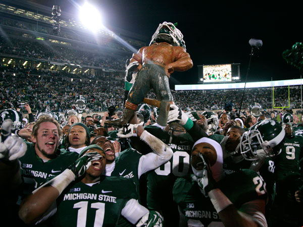 Michigan State players celebrate with the Paul Bunyon Trophy following their 29-6 win over Michigan in an NCAA college football game, Saturday, Nov. 2, 2013, in East Lansing, Mich. (Al Goldis/AP)