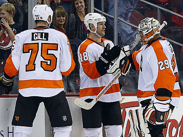The Flyers´ Adam Hall congratulates goalie Ray Emery as teammate Hal Gill watches. (Rich Schultz/AP)