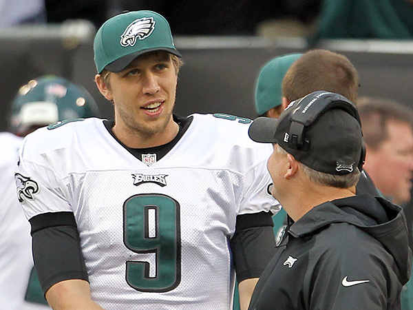 Eagle quarterback Nick Foles chats on the sideline Sunday with head coach Chip Kelly. (Yong Kim/Staff Photographer)