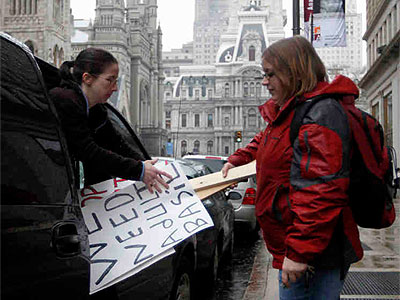 Natalie Ross (left) helps Philadelphia Unemployment Project´s Antoinette Kraus load signs into a van for a candlelight vigil in Harrisburg to protest the demise of the adultBasic program. (File Photo: Matt Rourke / Associated Press)