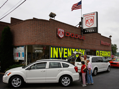 Tom Tague (center) who has been in sales for 21 years at Weathers Dodge, shows Angelina and Jose Caro their new 09 Dodge Caliber. (Michael S. Wirtz / Staff Photographer)