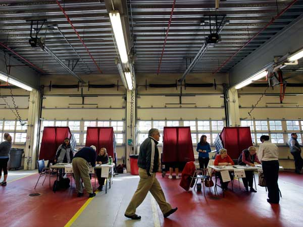 Poll workers and voters are seen in the Mendham Township, N.J., fire hall on election day, Tuesday, Nov. 5, 2013. (AP Photo/Mel Evans)
