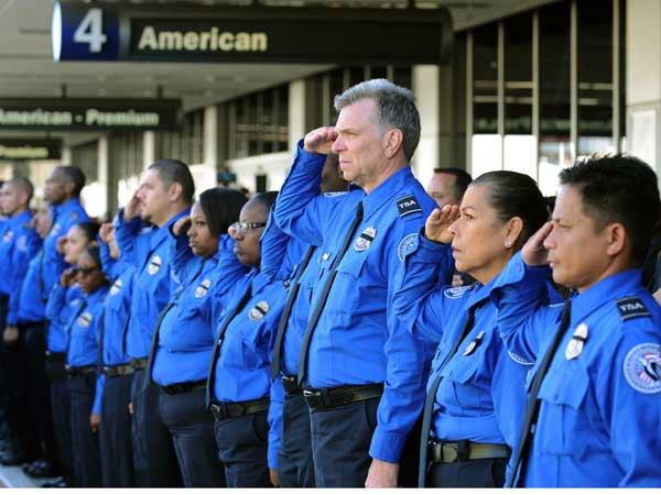 A long line of Transportation Security Administration personnel salute the U.S. Honor Flag procession as it leaves Los Angeles International Airport at Los Angeles International Airport in memory of TSA agent Gerardo Hernandez. (AP photo)