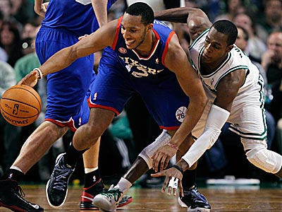 Sixers guard Evan Turner and Celtics guard Rajon Rondo scramble for a loose ball in the first half on Friday night. (Michael Dwyer/AP)